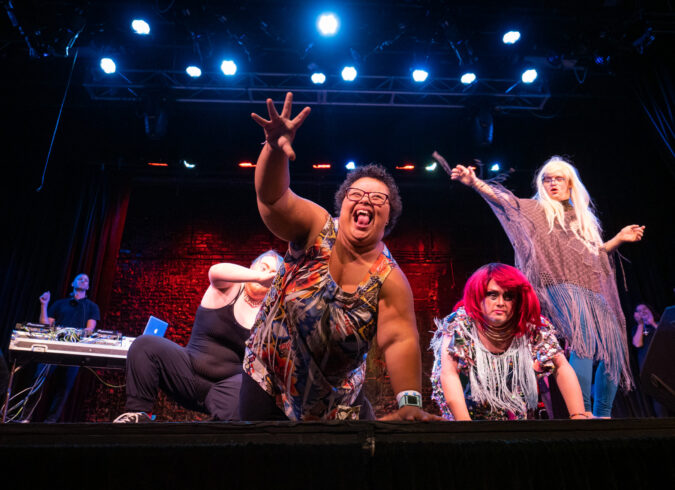 Photo of four performers on stage during the 2019 Disability Drag Show. A woman with Down syndrome is on all fours with her right arm outstretched and grabbing for the audience. Her face is full of joy.