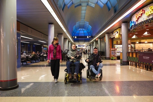 Two men in electronic wheelchairs and a female walking down the corridor of a busy airport.